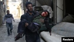 A man carries an injured boy in the rebel-held besieged town of Hamouriyeh, eastern Ghouta, near Damascus, Syria, Feb. 21, 2018.