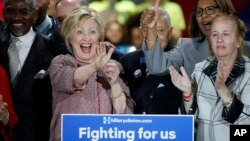 Flanked by supporters, Democratic presidential candidate Hillary Clinton, second from left, celebrates after winning the New York primary election, Tuesday night, April 19, 2016.