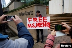 FILE - A man holds a sign outside of the B.C. Supreme Court bail hearing of Huawei CFO Meng Wanzhou, who is being held on an extradition warrant in Vancouver, British Columbia, Canada, Dec. 10, 2018.