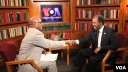 VOA's Somali Chief Abdirahman Yabarow (left) greets President Hassan Sheikh Mohamud