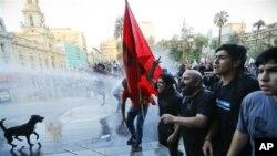 Polisi anti huru hara menyemprotkan air untuk memubarkan para pengunjuk rasa yang berpartisipasi dalam demo KTT Rakyat yang diselenggarakan oleh serikat buruh dan gerakan sosial kiri. Demo ini menentang pelaksanaan KTT 60 negara yang dijadwalkan akan diselenggarakan akhir pekan ini di Santiago, Chile (25/1).