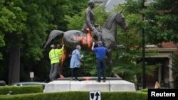 Trabajadores municipales intentan remover la pintura sobre un monumento al soldado confederado John B. Castleman que fue vandalizada el sábado por la noche en Louisville, Kentucky.