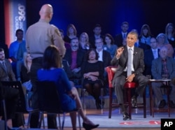 President Barack Obama answers questions from Arizona Sheriff Paul Babeu, standing at left, during a CNN televised town-hall meeting at George Mason University in Fairfax, Va., Jan. 7, 2016.