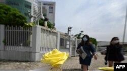 一枚黃色玫瑰被擺放在香港蘋果日報總部樓外。(2021年6月22日)