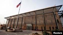 FILE - A U.S. flag flies in front of the Chancellery building inside the compound of the U.S. Embassy in Baghdad, Dec. 14, 2011.