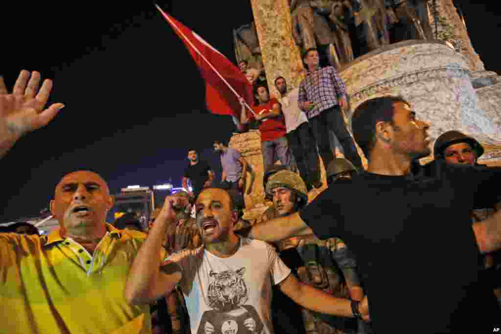 Supporters of Turkey's President Recep Tayyip Erdogan protest in front of soldiers in Istanbul's Taksim square, early Saturday, July 16, 2016.