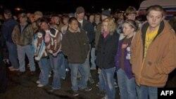 Học sinh và phụ huynh đứng ở bãi đậu xe gần trường trung học Marinette để chờ tin tức về vụ bắt con tin, ngày 30/11/2010