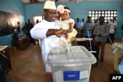Sierra Leone's People Party presidential candidate Julius Mada Bio holds his daughter while casting his ballot for the general elections, at a polling station in Freetown, March 7, 2018.