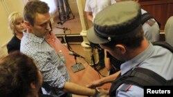 Một nhân viên Bộ Nội vụ còng tay lãnh tụ đối lập Nga Alexei Navalny trong phòng xử án ở Kirov, ngày 18 tháng 7, 2013.