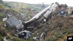 Rescue workers walk among the crash site of a cargo airplane near the airport at Brazzaville in the Republic of Congo on Dec. 1, 2012.