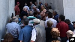 29일 그리스 항구도시 태살로니키에서 연금을 받으려는 사람들이 폐쇄한 은행 앞에 줄 서 있다.
