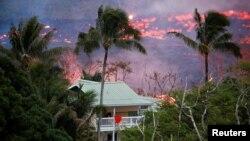 La lava del volcán Kilauea en Hawái fluye cerca de una casa en las afueras de Pahoa, durante una erupción. Mayo 19, de 2018.