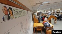 FILE - A genealogy chart of Mormon church founder Joseph Smith hangs on a wall as people research records to work on their genealogy in the Family History Library of The Church of Jesus Christ of Latter-Day Saints on the campus of Brigham Young University