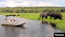 FILE - Foreign tourists in safari riverboats observe elephants along the Chobe River bank in Chobe National Park, in northern Botswana, March 2005.