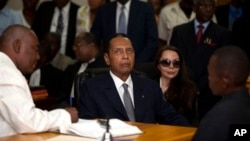 """Former Haitian dictator Jean-Claude """"Baby Doc"""" Duvalier, center, attends hearing as companion Veronique Roy sits behind, right, Port-au-Prince, Feb. 28, 2013."""