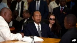"Former Haitian dictator Jean-Claude ""Baby Doc"" Duvalier, center, attends hearing as companion Veronique Roy sits behind, right, Port-au-Prince, Feb. 28, 2013."
