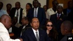 """Mantan diktator Haiti Jean-Claude """"Baby Doc"""" Duvalier (tengah) didampingi pacarnya Veronique Roy (kanan) menghadiri sidang di Port-au-Prince (28/2)."""