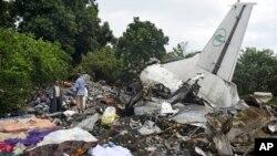 Quelques personnes fouillent les restes de l'épave d'un avion-cargo qui est écrasé dans la capitale, Juba, Sud-Soudan, 4 novembre 2015. (AP Photo/Jason Patinkin)