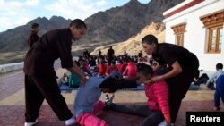 The nuns help participants stretch their muscles during a five-day workshop teaching young women the martial art of Kung Fu, in Hemis region in Ladakh, India, August 18, 2017.