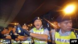 Cảnh sát Hong Kong xịt hơi cay vào người biểu tình khi họ cố vượt qua hàng rào cảnh sát ở trung tâm thương mại của Hong Kong, 1/7/2011