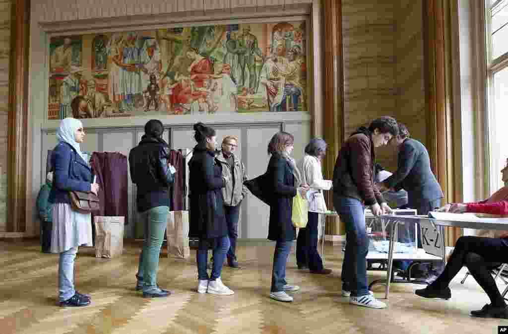 Residentes de París hacen fila ante una mesa electoral. (AP)