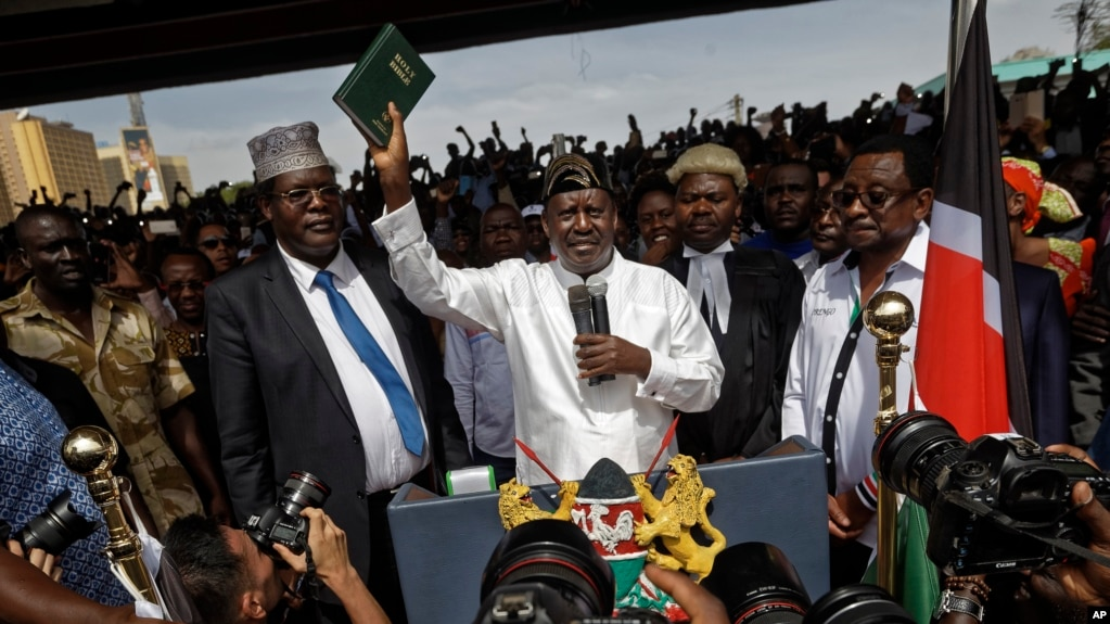 "FILE - Opposition leader Raila Odinga, center, accompanied by lawyers Miguna Miguna, center-left, Tom ""T.J."" Kajwang, center-right, and politician James Orengo, right, holds a Bible aloft after a mock ""swearing-in"" ceremony at Uhuru Park in downtown Nairobi, Kenya, Jan. 30, 2018."