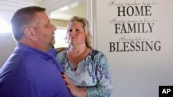 Laurie and Jason Holt look stand for a photo during an interview at their home, June 28, 2017, in Riverton, Utah.