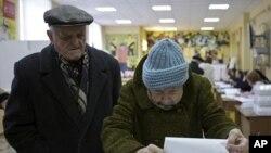 一对俄罗斯老年夫妇3月4日在莫斯科一个投票站为总统大选投票