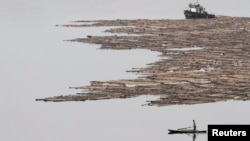 FILE - A North Korean man rows a boat past logs, which were tied together and transported by boats on the Yalu River near the North Korean city of Hyesan, Aug. 16, 2014.