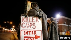 17일 미국 미주리주 퍼거슨 시 경찰서 앞 시위대가 흑인 청년 마이클 브라운이 경찰의 총에 맞아 사망한 사건과 관련하여 항의하고 있다.
