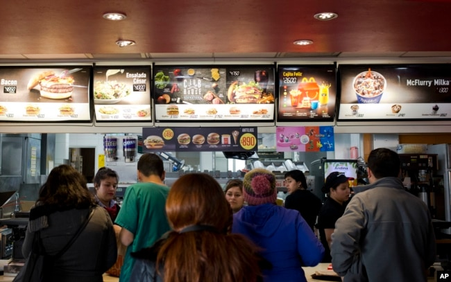 Customers stand in line at a fast food restaurant in Santiago, Chile, June 22, 2016.