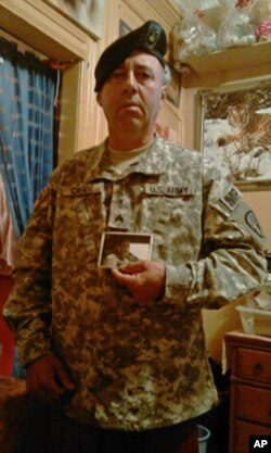 Sgt. Carde, who was wounded in Iraq, keeps a picture of his fallen comrade in his living room.