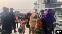 Rohingya refugees stand in a queue after they disembarked from a Bangladesh Navy ship to the island of Bashar Char in Noakhali on December 4, 2020.