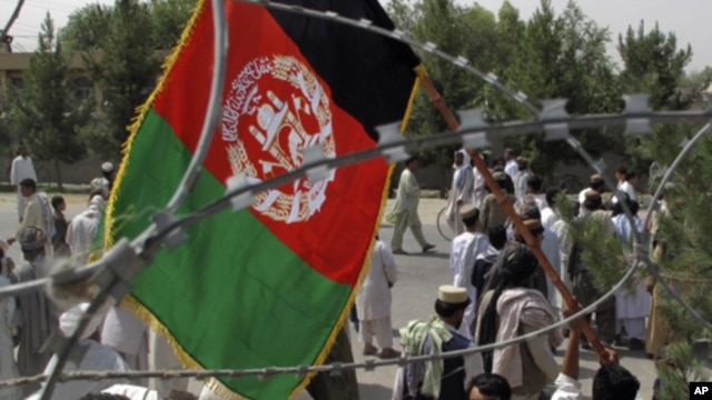 An Afghan man holds Afghanistan's flag during an anti-Pakistan protest in Helmand province, Afghanistan, July 11, 2011.