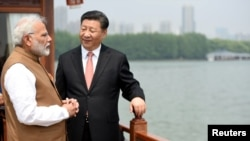 India's Prime Minister Narendra Modi speaks with Chinese President Xi Jinping as they take a boat ride on the East Lake in Wuhan, China, April 28, 2018.