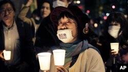 "Seorang perempuan mengenakan masker bertuliskan ""Hilangkan Nuklir"" dalam peringatan 25 tahun bencana Chernobyl dan protes di depan kantor pusat Tokyo Electric Power Company (TEPCO). (Foto: Dok)"