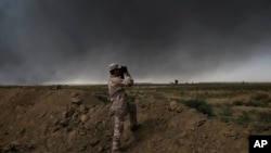 An Iraqi army member looks toward so-called Islamic State group territory outside Qayyarah on Tuesday Oct. 4, 2016.