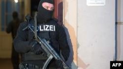 Сотрудник полиции в Берлине блокирует вход в жилое здание, где проводился рейд против предполагаемых террорситов. Германия. 16 января 2015 г.