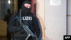 2014年1月16日,一名德国警官在柏林的一栋公寓对极端分子嫌疑人的住处进行搜查后站在这栋公寓外面站岗。