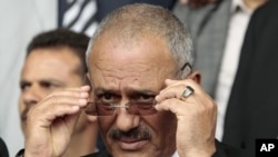 Yemen's President Ali Abdullah Saleh adjusts his glasses during a rally in Sana'a, April 22, 2011