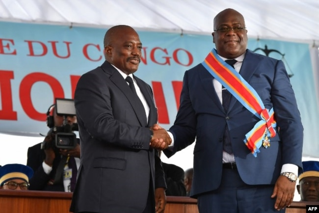 FILE - Democratic Republic of the Congo's outgoing President Joseph Kabila, left, shakes hands with newly inaugurated President Felix Tshisekedi after he was sworn-in in Kinshasa, Jan. 24, 2019.