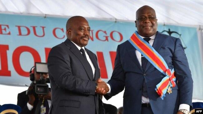 Le 24 janvier 2019, le président sortant de la République démocratique du Congo, Joseph Kabila, serre la main du président nouvellement élu, Felix Tshisekedi, après l'avoir assermenté à Kinshasa.