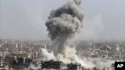 FILE - Smoke rises after shelling by the Syrian army, after Russian airstrikes, in Damascus, Syria, Oct. 14, 2015.