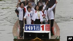 Yingluck Shinawatra, center, opposition Pheu Thai Party's candidate for prime minister and youngest sister of ousted PM Thaksin Shinawatra, gestures from a boat during her election campaign rally at a canal on the outskirts of Bangkok, Thailand, June 30,