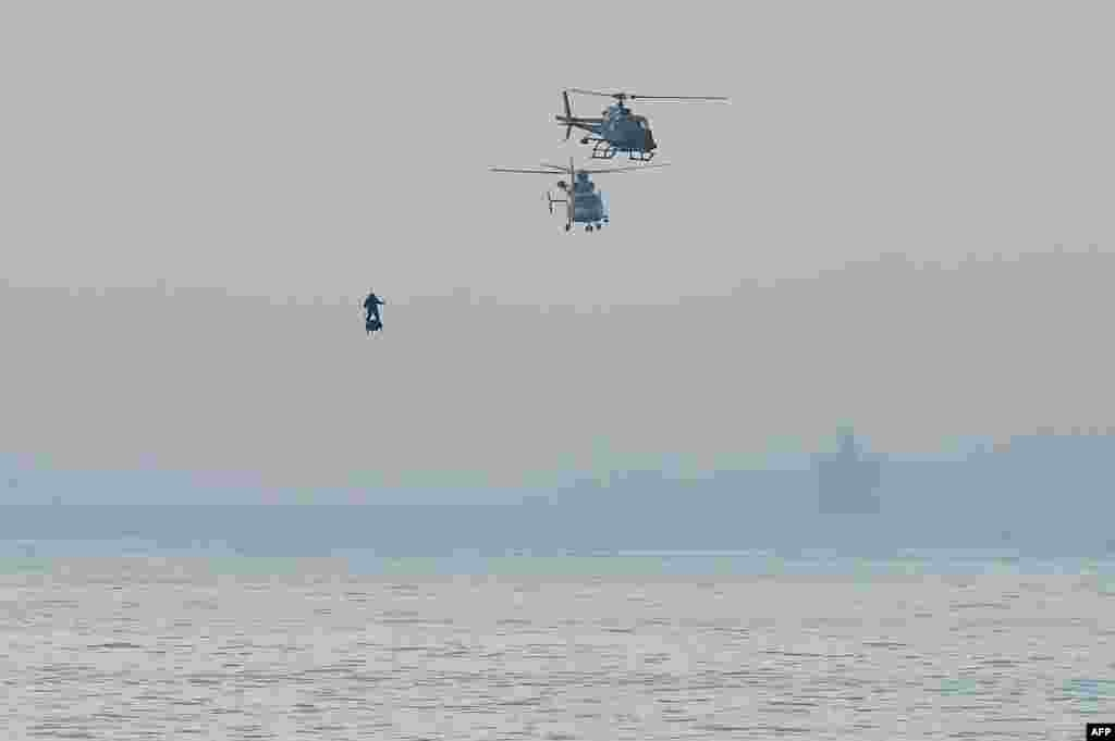 "Franky Zapata on his jet-powered ""flyboard"" arrives at St. Margaret's Bay in Dover, England, during his attempt to fly across the 35-kilometer (22-mile) English Channel crossing in 20 minutes, with an average speed of 140 kilometers an hour (87 mph) at a height of 15-20 meters (50-65 feet) above the sea."