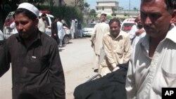 Cư dân khiêng xác nạn nhân vụ tấn công ở khu vực ngoại ô Peshawar, Pakistan, ngày 2/4/2013.