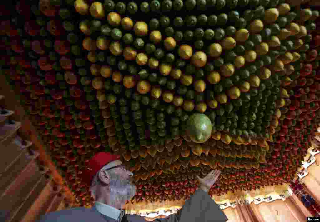 A member of the Samaritan sect decorates a traditional hut known as a sukkah with fruits and vegetables on Mount Gerizim, on the outskirts of the West Bank City of Nablus. A sukkah is a ritual hut used during the week-long Jewish holiday of Sukkot which begins Oct. 6 at sundown.