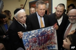 Republican presidential candidate, Ohio Gov. John Kasich, looks at a picture of the White House made by students at a religious school in the Brooklyn borough of New York, April 12, 2016.