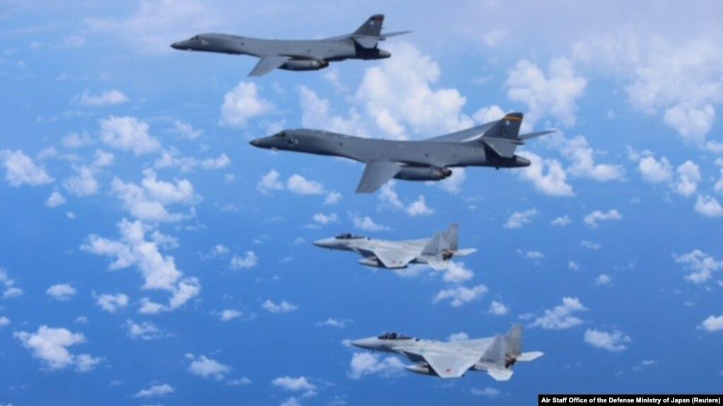 Những chiếc đấu cơ F-15 của Nhật Bản (dưới) diễn tập với máy bay ném bom B-1B Lancer của Mỹ (trên) trong vùng trời bên trên Biển Hoa Đông, Nhật Bản, trong một bức hình do Văn phòng Tham mưu Không quân của Bộ Quốc phòng Nhật Bản công bố ngày 9 tháng 9, 2017.