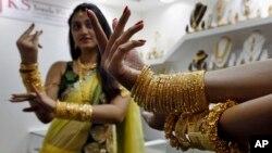 Dua orang model memeragakan perhiasan emas yang dikenakannya dalam sebuah pameran emas dan permata di Hyderabad, India (7/6).